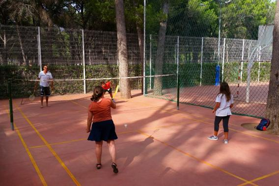 Three people playing a game of badminton